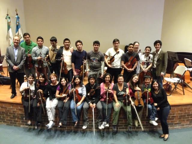 Craig Mumm posing on stage with 20 youth holding stringed instruments.