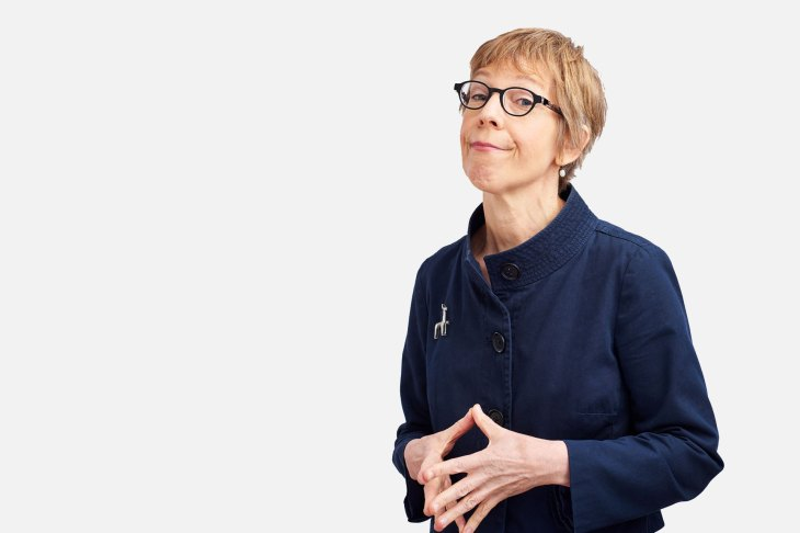 Angela Beeching in a navy coat and black glasses posing in front of a white background with a pensive expression.