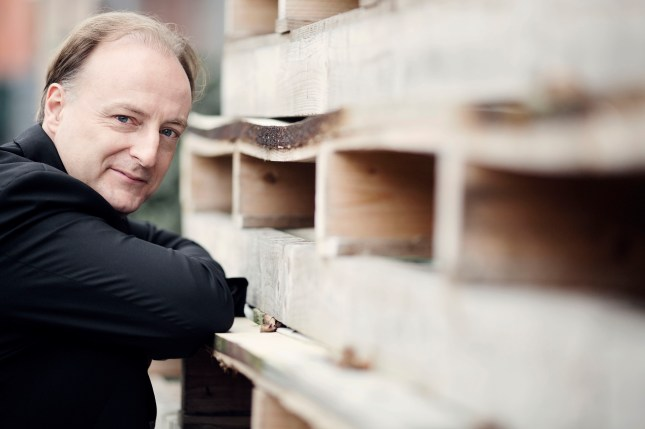 Christoph-Mathias Mueller leaning against a pile of wood pallets.  Posing in a black suit coat.
