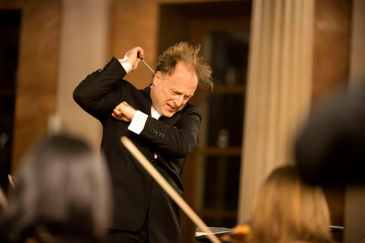 Christoph-Mathias Mueller conducting enthusiastically in front of the orchestra, wearing a tuxedo.
