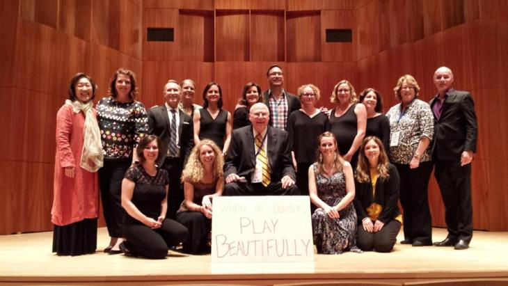 Group photo of former graduates of the Eastman school, posing on stage at Eastman with their teacher, Richard Killmer.