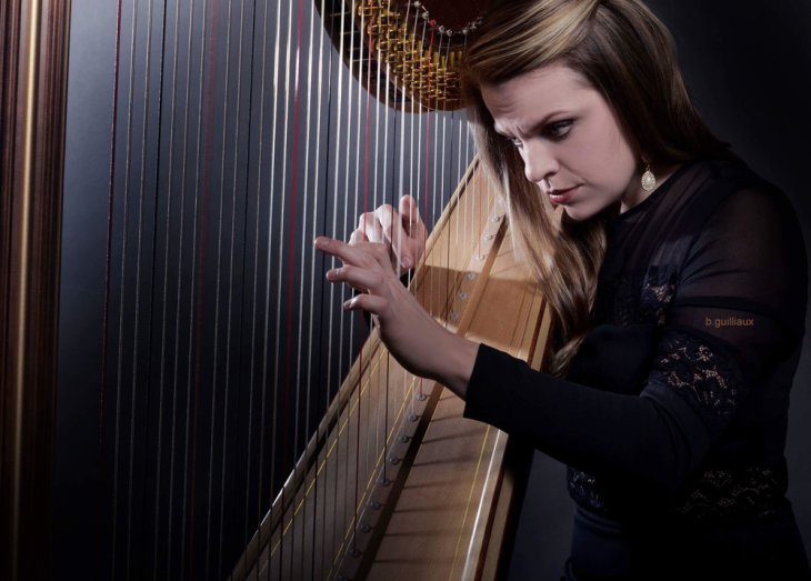 Grace Browning in concert black focusing on performing her harp in a dark colored head shot.