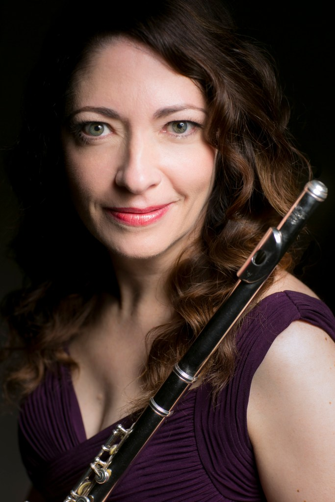 Christina Smith in a deep purple gown, posing for a portrait with her flute and a dark background.