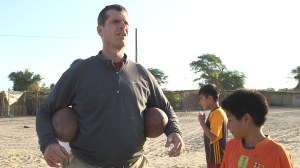 Jim Harbaugh talks football with children in the Piura.