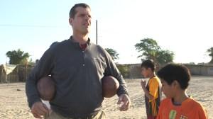Jim Harbaugh talks football with children in the Piura.