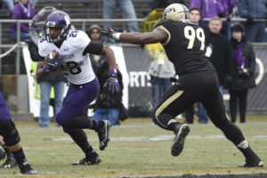 Nov 22, 2014; West Lafayette, IN, USA; Northwestern Wildcats running back Justin Jackson (28) runs past Purdue Boilermakers defensive end Ryan Russell (99) in the 2nd half at Ross Ade Stadium. Northwestern won the game 38-14.Mandatory Credit: Sandra Dukes-USA TODAY Sports