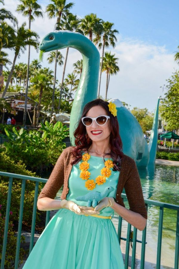 Theresa Disneybounding as Clarice the Chipmunk, standing in front of Gertie the Dinosaur, holding a small crocheted dinosaur.