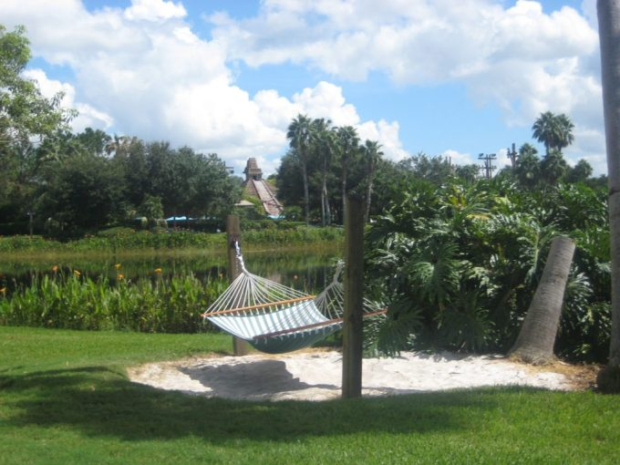 A single hammock above a patch of sand with a Mayan temple across a lake in the background on a sunny day.
