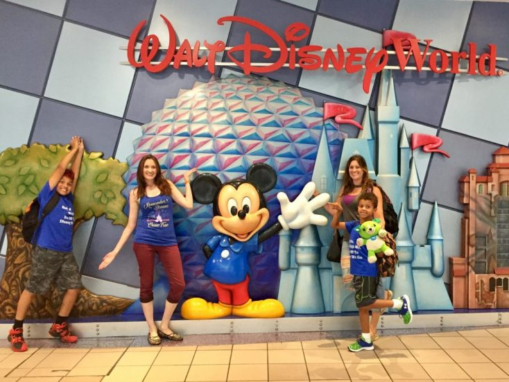 Theresa, her sister, and nephews doing silly poses in front of the Walt Disney World mural at the Orlando International Airport