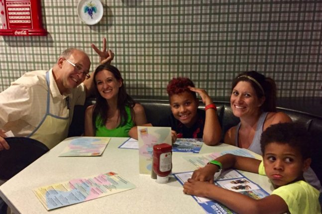The server at 50's Prime Time Cafe giving Theresa bunny ears as she and her family pose for a photo at their table