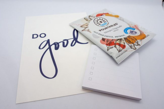 "Notecard with ""Do Good"" printed on top, small notepad with lines and check marks, and Pourtables coffee package."