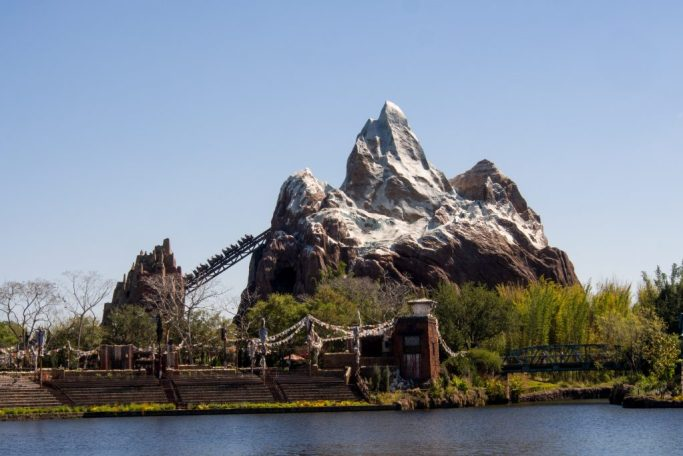 Waterfront view of the Expedition Everest roller coaster at Disney's Animal Kingdom with a clear blue sky.