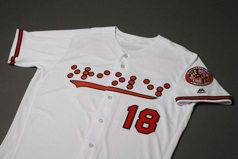 White Orioles jersey with the team name in orange Braille lettering laying on a gray background.