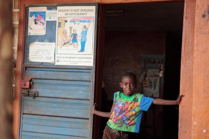 Young boy in Sierra Leone leaning next to poster providing awareness raising information about epilepsy