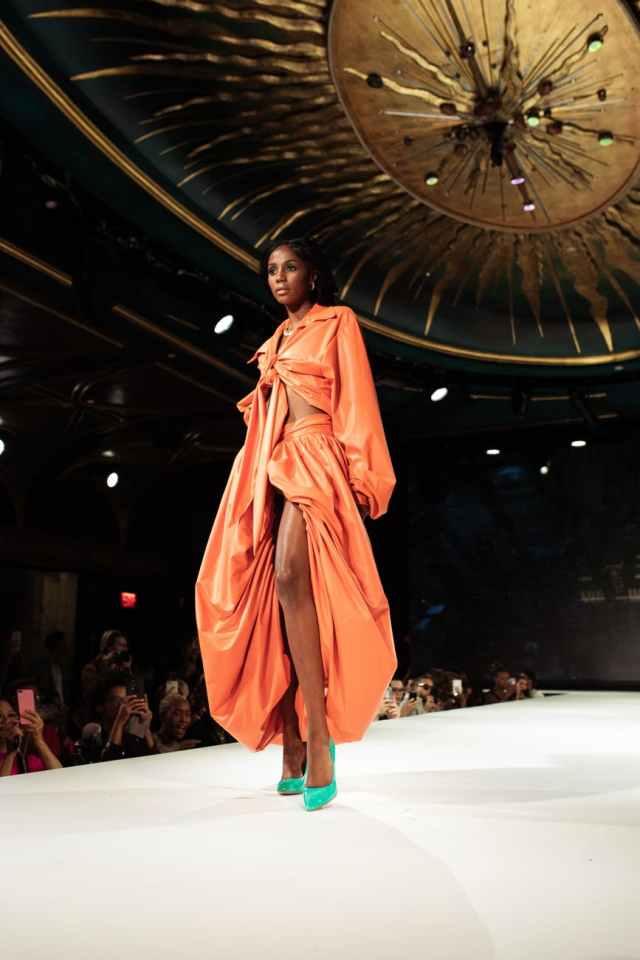 woman in orange robe standing on white floor