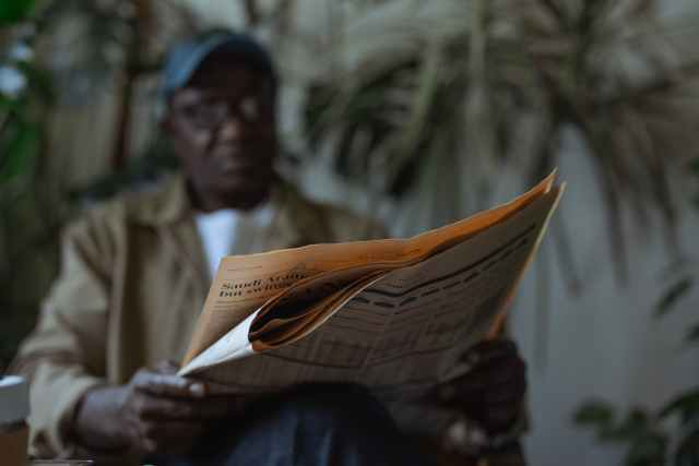 low angle photo of man reading newspaper