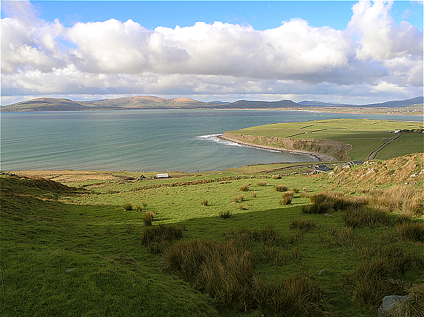Ballinskelligs Bay on the west coast of Ireland with green fields in the foreground, mountains in the distance and clouds in a blue sky.