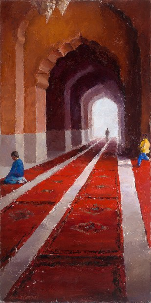 View of people inside the Jama Masjid mosque in Delhi, India, showing red carpets receding into the background underneath curved archways.