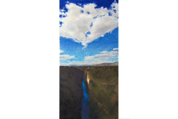 Bright white clouds above the Rio Grande Gorge with a spot of bright sunlight in the shadow area of the rocky wall as seen from the bridge in Taos, New Mexico.