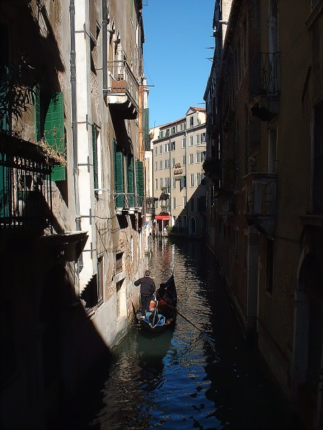 Canal in Venice with gondola in foreground between rows of buildings in light and shadow.