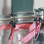 close up of glass jars with ribbon around necks