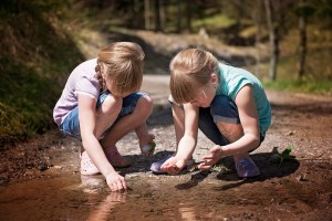 2 girls gathering stones by river