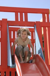 girl in playground on slide
