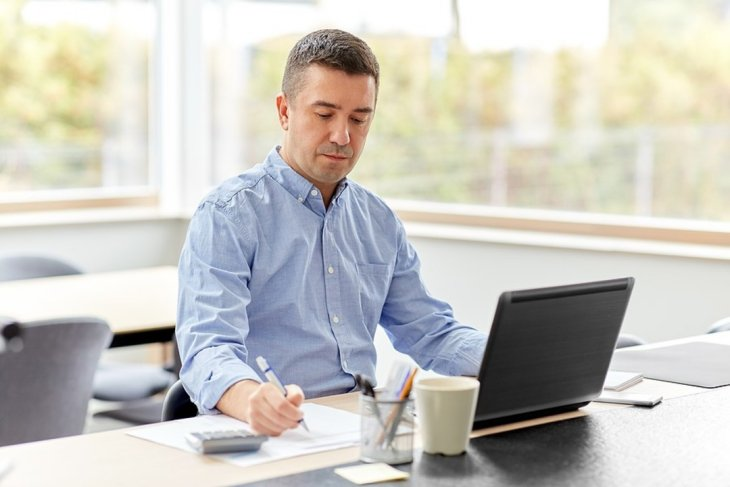 Man sitting at his desk writing on a document.