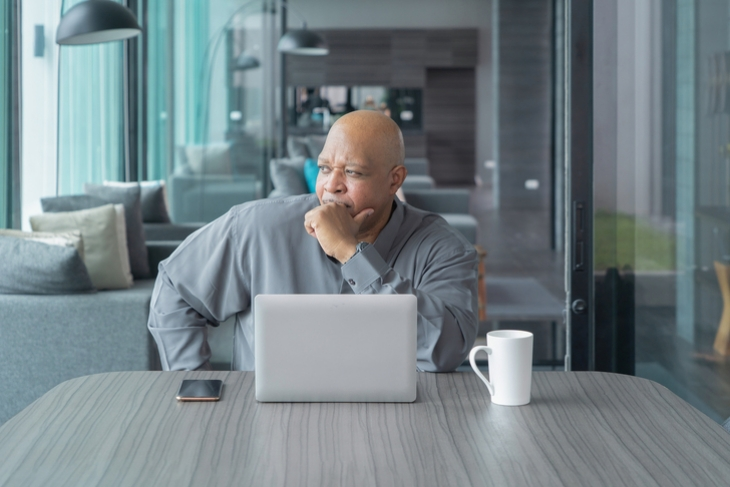 Man sitting at his desk looking out a window.