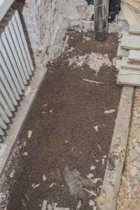 Lattiarakenteen koolausten välissä olevia leca-papuja, kutteria sekä betonivalun jätepaloja