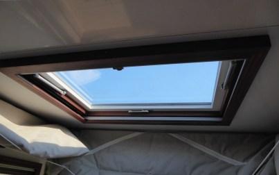 Dachfenster mit Rollos und Holzrahmen