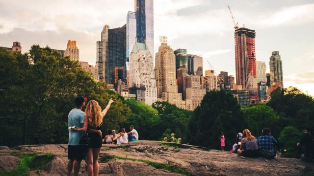 Mladé páry v parku za městem, v pozadí výškové budovy