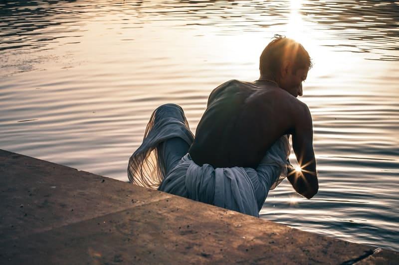 holy indian man bathing in a holy lake during sunrise
