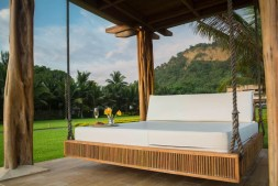 brown wooden framed white mattress hanging bed surrounded by green grass