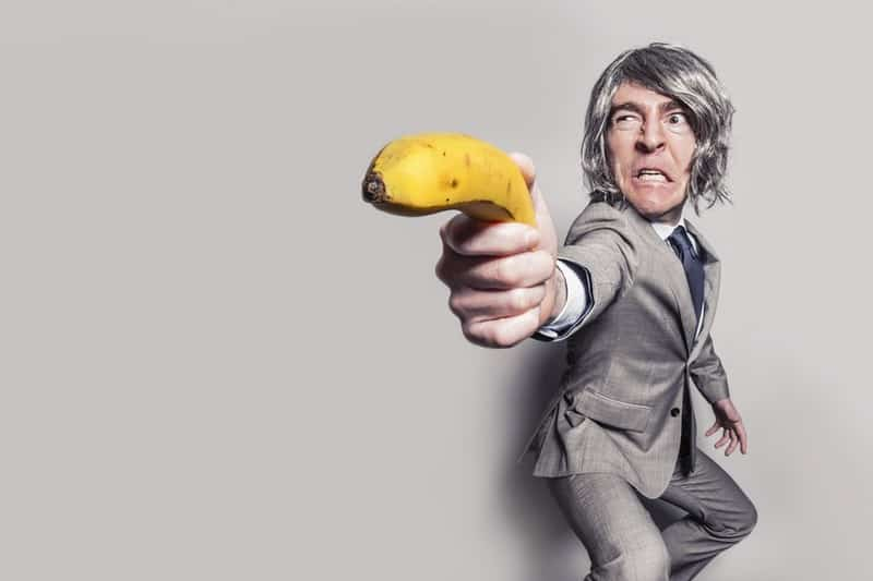 man-in-gray-suit-jacket-holding-yellow-banana-fruit-while-making-face