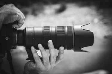 black camera lens taking a photo