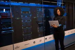 woman standing inside a large server room-min