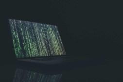 Green Matrix like code a Laptop inside a Dark Office