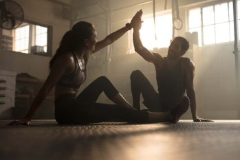 A woman and a man are sitting on the floor of a gym and giving each other high five.