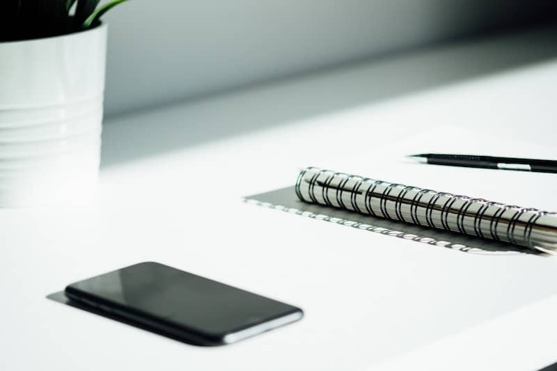 Iphone and a notepad laying on top of a white office desk