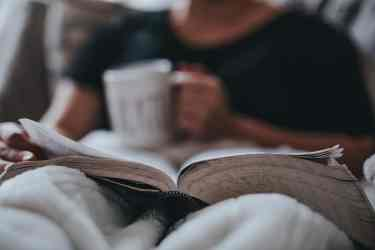 Man reading a book while drinking coffee in his bed