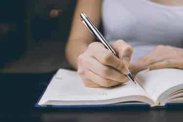 Woman getting ready to write in her notebook