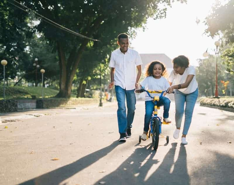 family teaching their daughter how to ride a bicycle-min