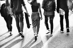 Group of Skateboarding Kids Walking Down The Road