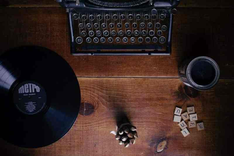 Scrabble pieces laying next to a vintage typewriter