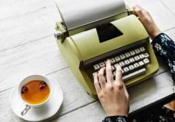 Woman typing on a vintage green typewriter