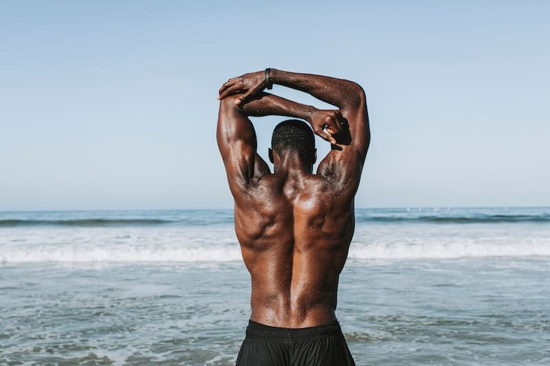 man at the beach stretching his arms