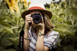 woman holding a DSLR camera in a sunflower field