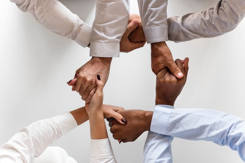 Business people holding each others hands creatively