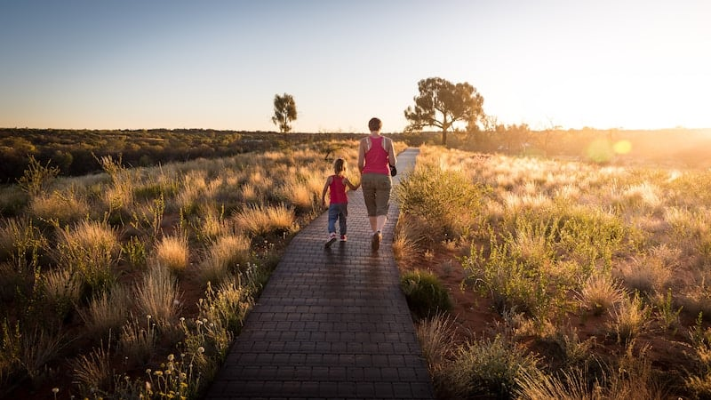 mother and daughter walking on a wooden path into the sunset